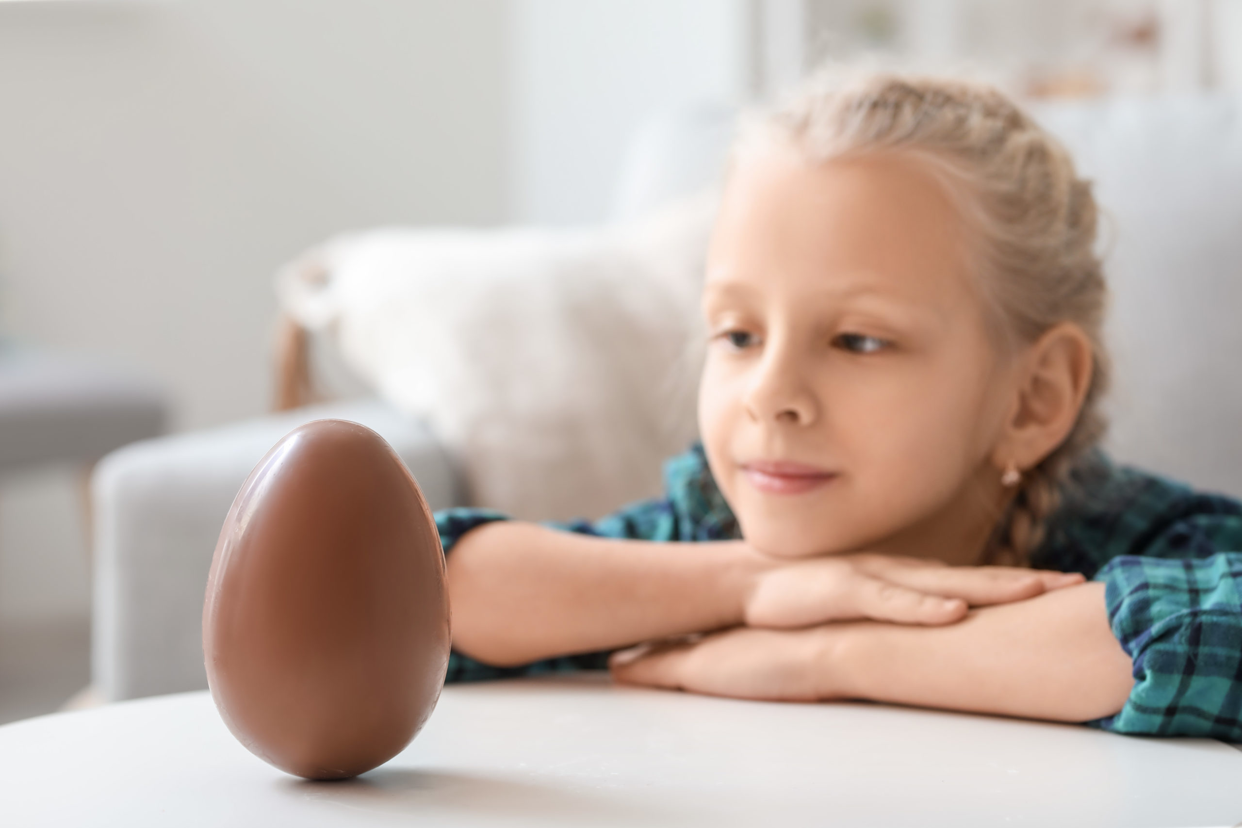 Cute little girl with sweet chocolate egg at home